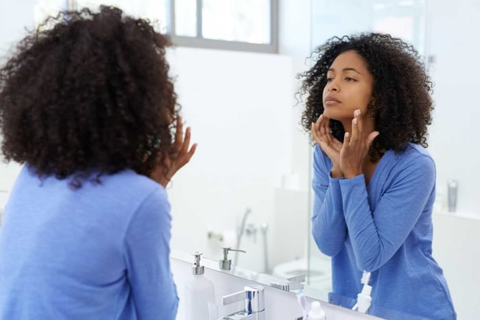woman applying product on her face in mirror