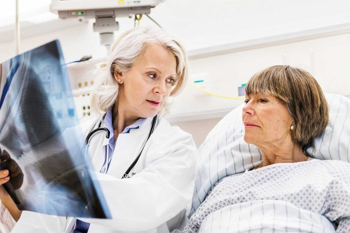 Female doctor discussing a scan result with her hospitalized patient.