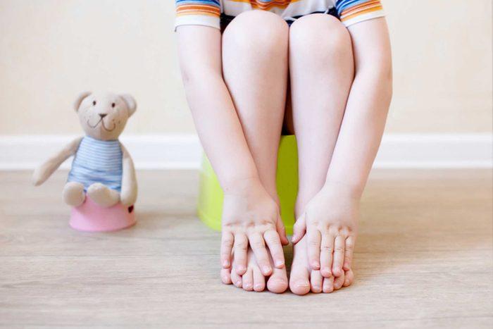 toddler on a training potty next to teddy bear on a mini potty