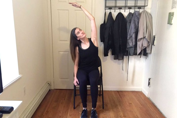 Woman sitting in a chair doing an overhead stretch.