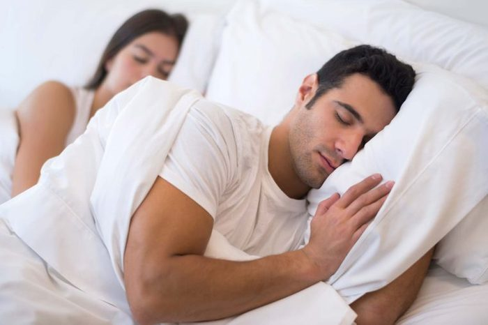 Man and woman sleeping with extra pillows