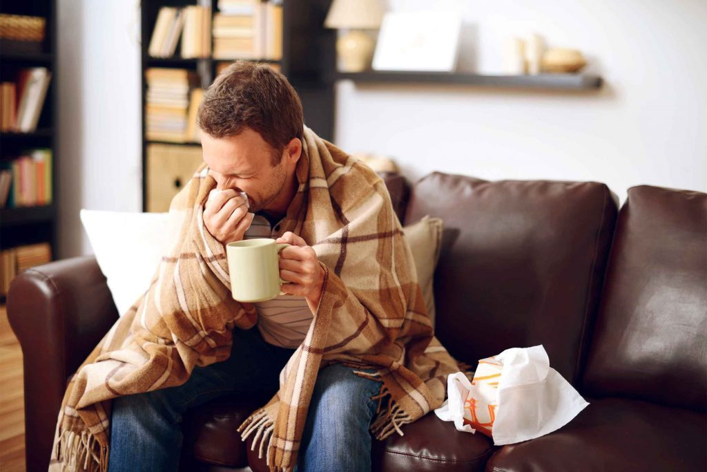 man with blanket on couch