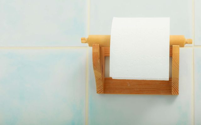 roll of toilet paper on wooden holder
