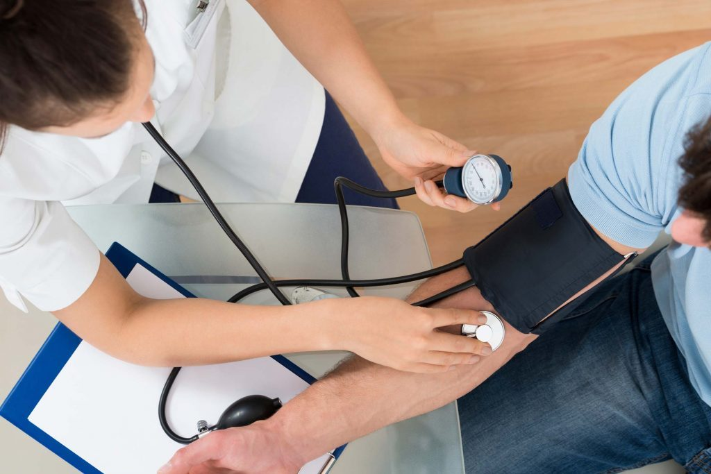 nurse checking a patients blood pressure
