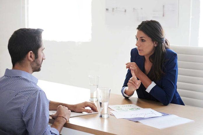 Woman talking to a man across from office desk