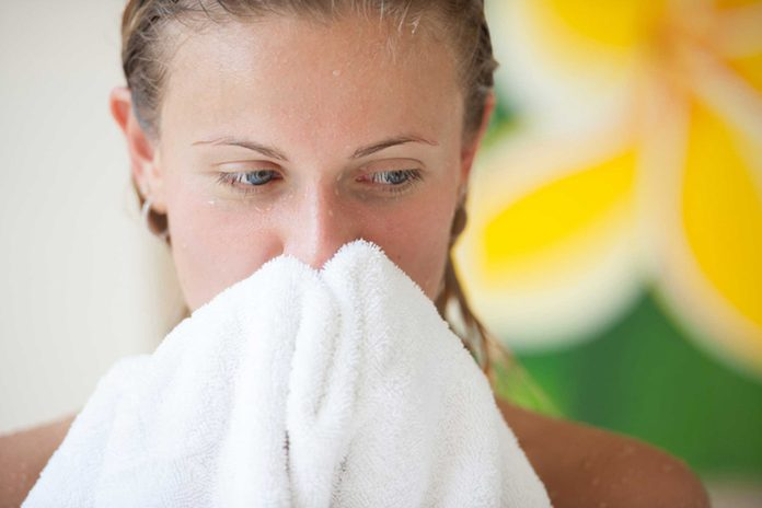 woman out of the shower, wiping her face with white towel