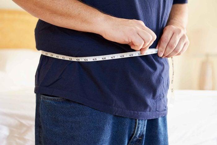 Man measuring his waistline