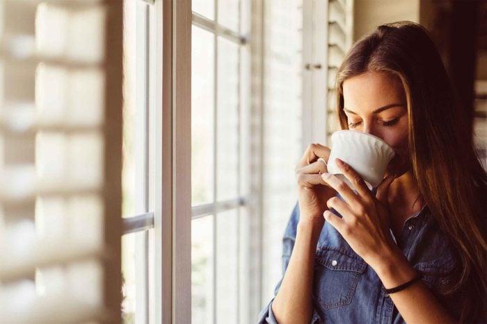 woman drinking tea by a window
