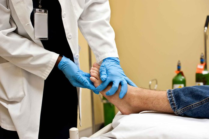 doctor checking patient's foot