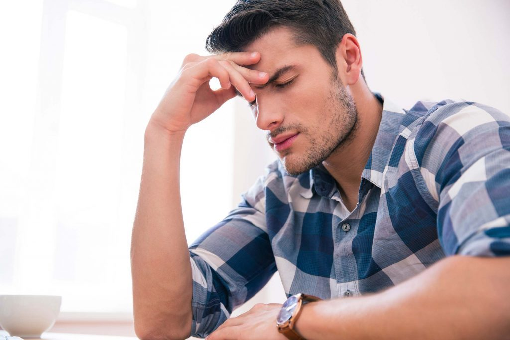 Man in a plaid shirt having a headache.