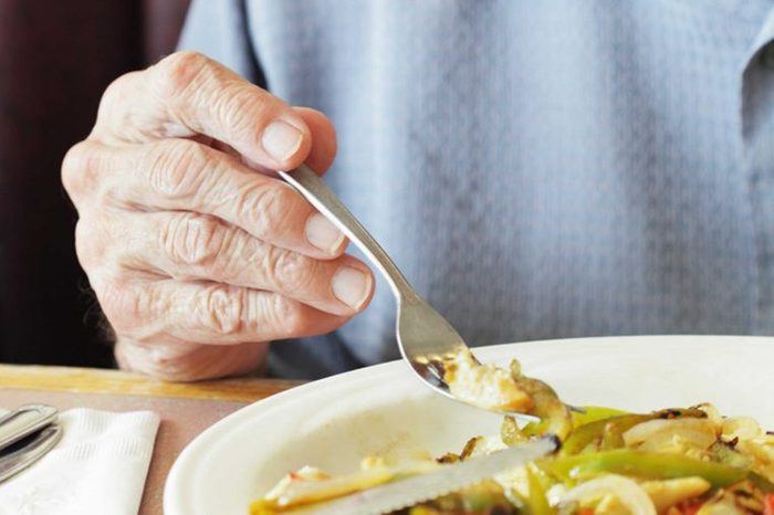 elderly person's hand holding a fork over meal