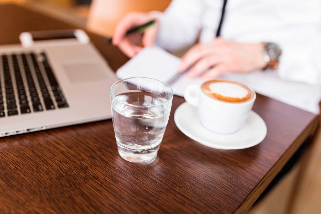 person at laptop computer with coffee and glass of water