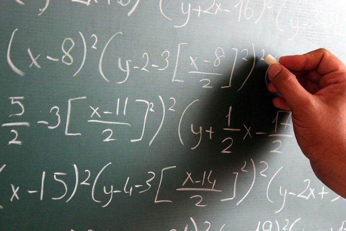 hand writing numbers on chalkboard