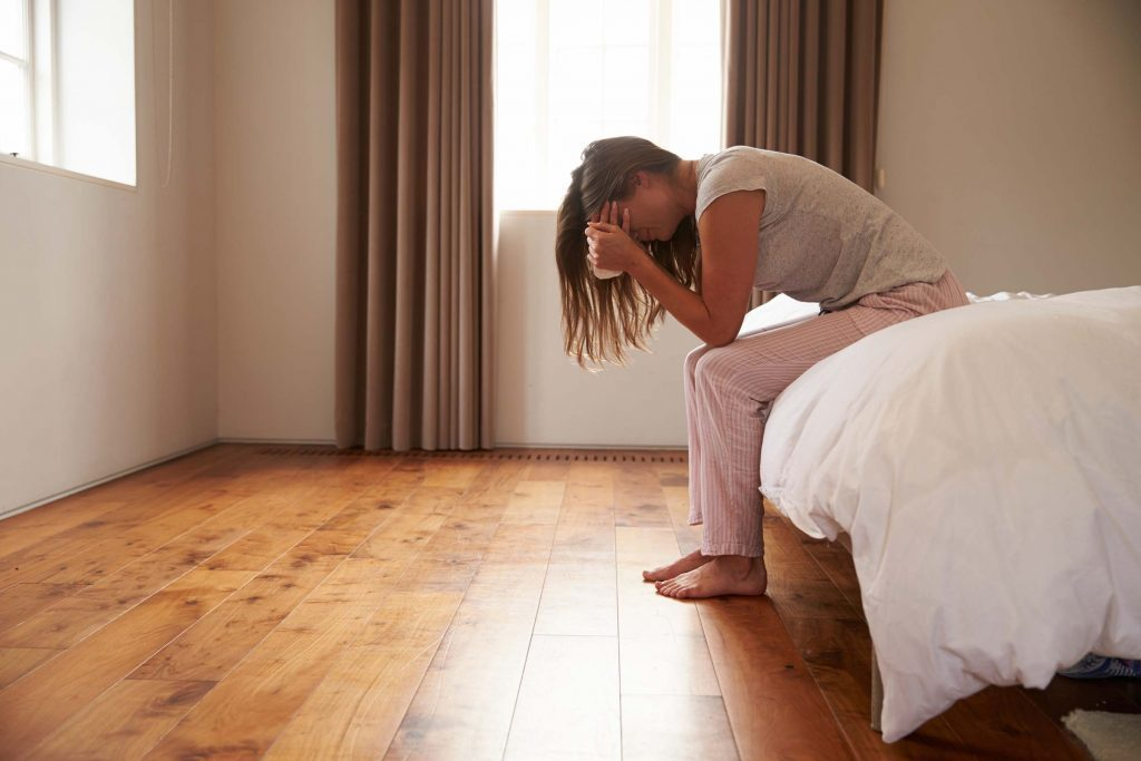 distraught woman holding her head in her hands and sitting on a bed