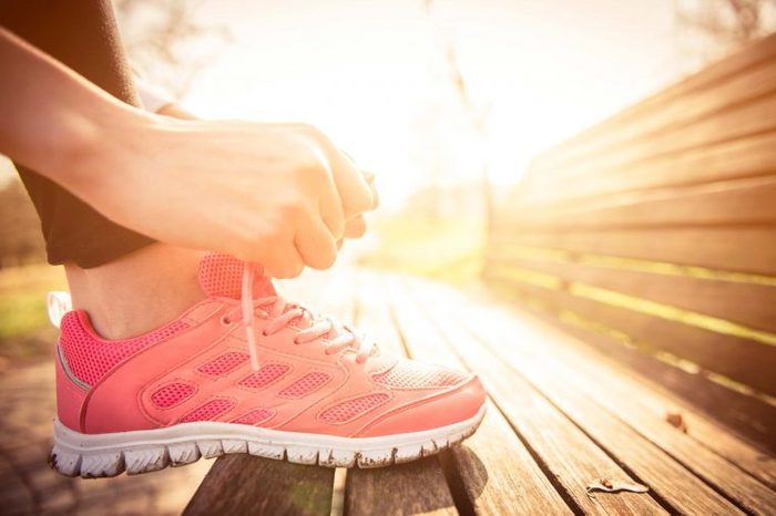 woman lacing up athletic shoe