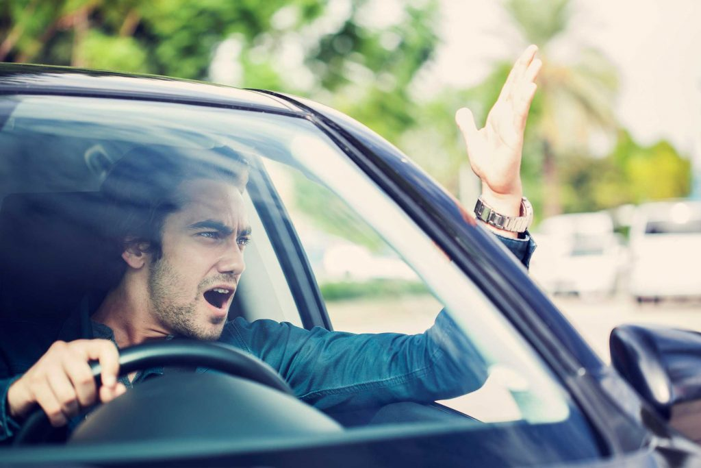 Man driving car yelling and gesturing out of the window