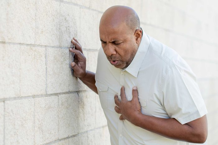 African American man in distress, hand over his chest.