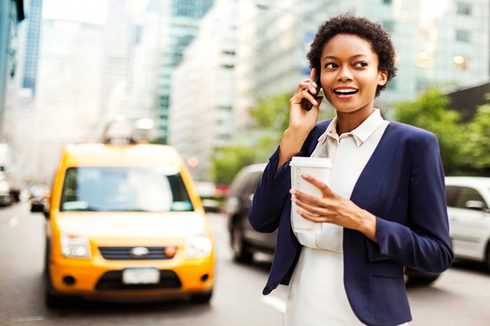 woman on street with to-go coffee, talking on cell phone