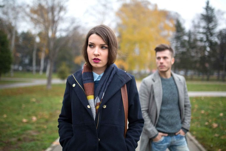 Woman wearing a coat and colorful scarf walking through a park as a man in a coat walks behind her.