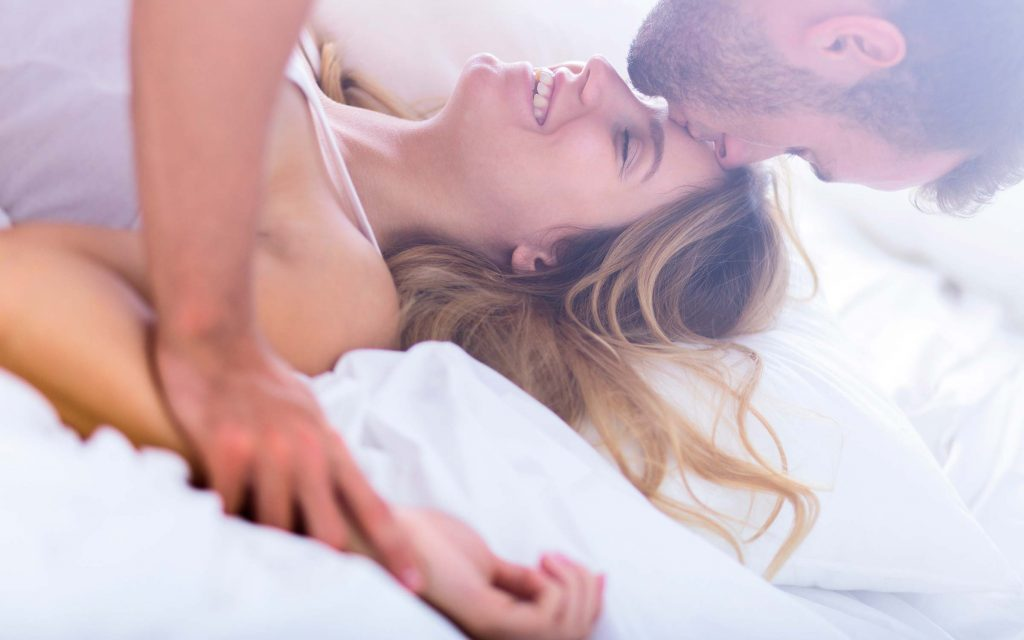 man embracing a woman in bed, both laughing