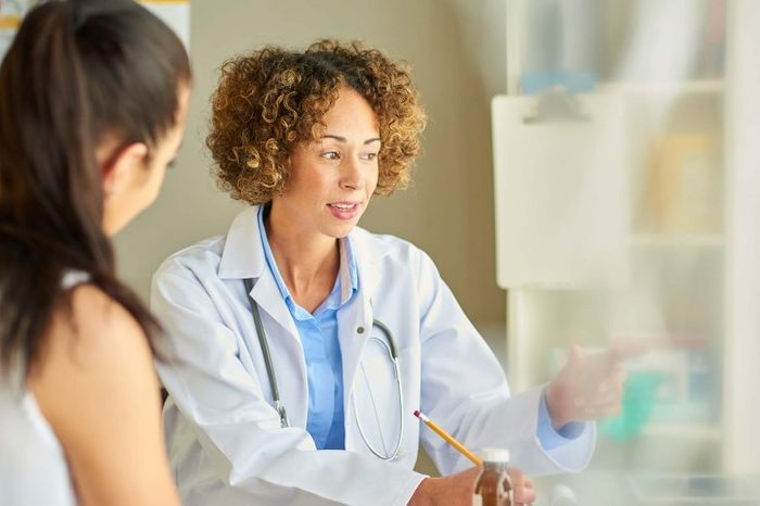 Woman doctor speaking to a woman patient in her office.