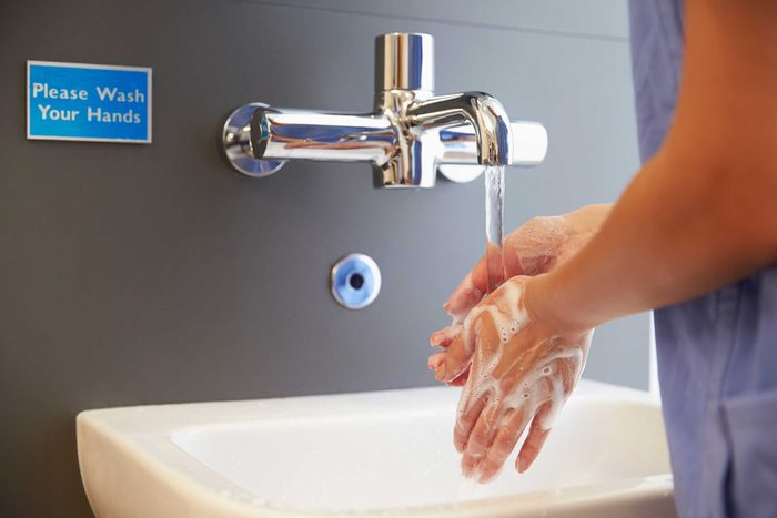 medical professional washing her hands with soap and water