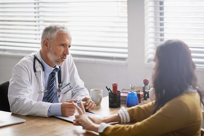 male doctor discussing diagnosis with female patient