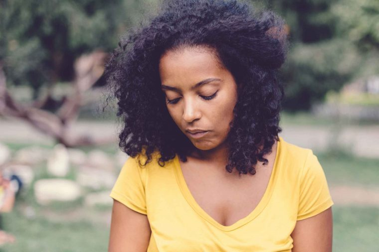 Woman in a yellow shirt standing in a park and looking depressed.