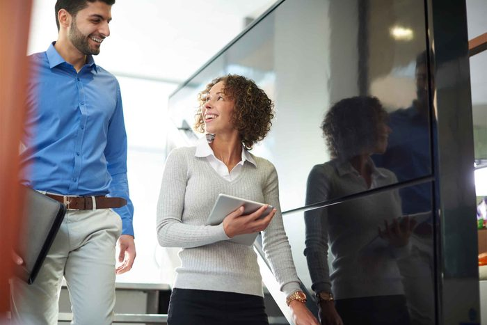 Male and female colleagues walking and talking at work