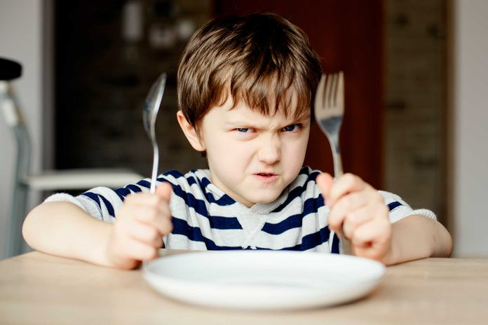 Angry child holding fork and knife in front of dinner plate