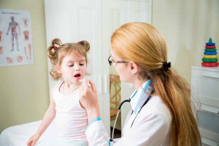 woman pediatrician examining a toddler girl