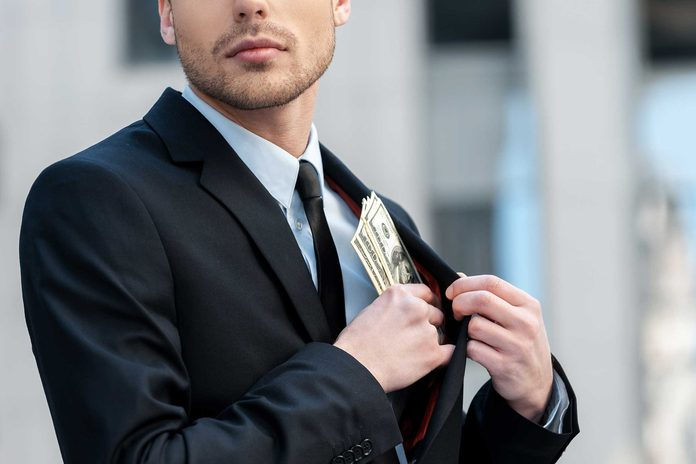 Man putting money into his inside suit pocket