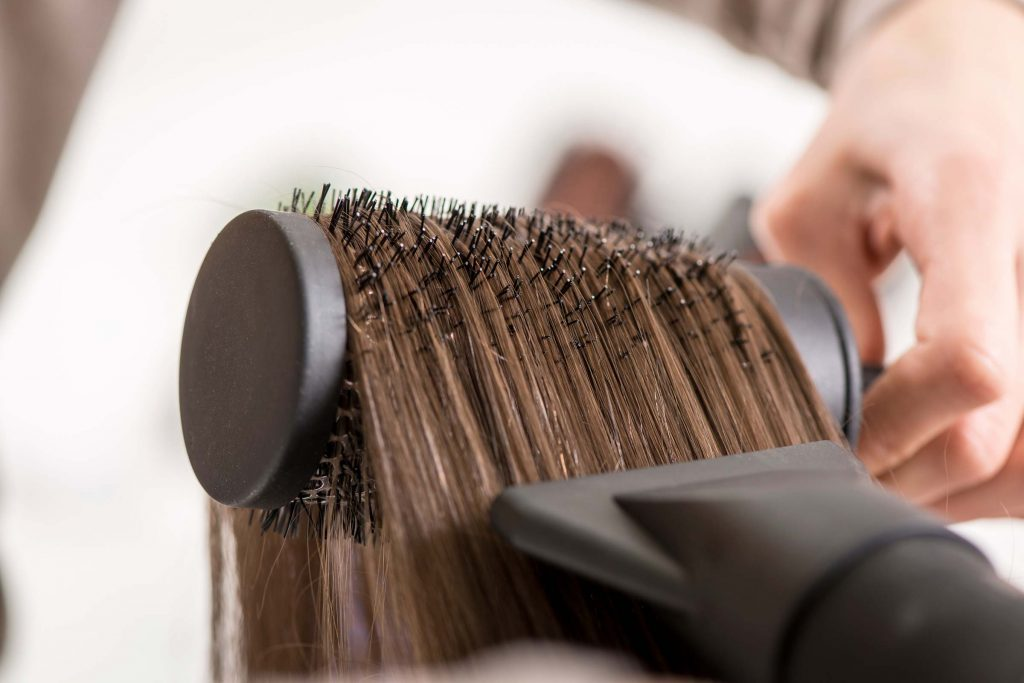 Person blowdrying their brown hair with a brush.