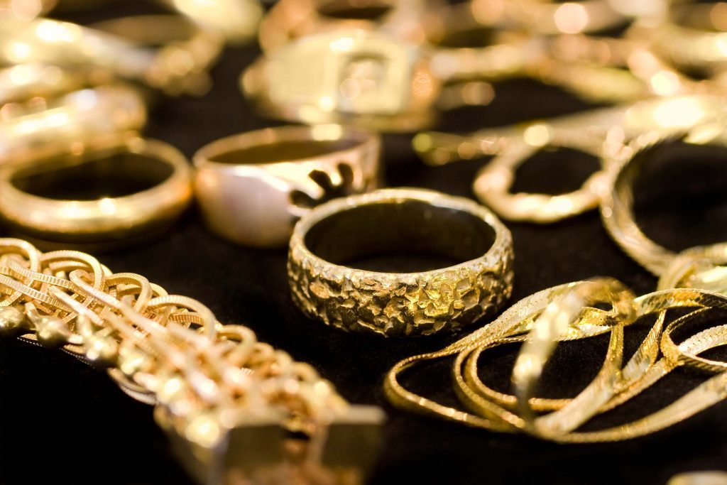 Rows of gold rings, bracelets and necklaces.