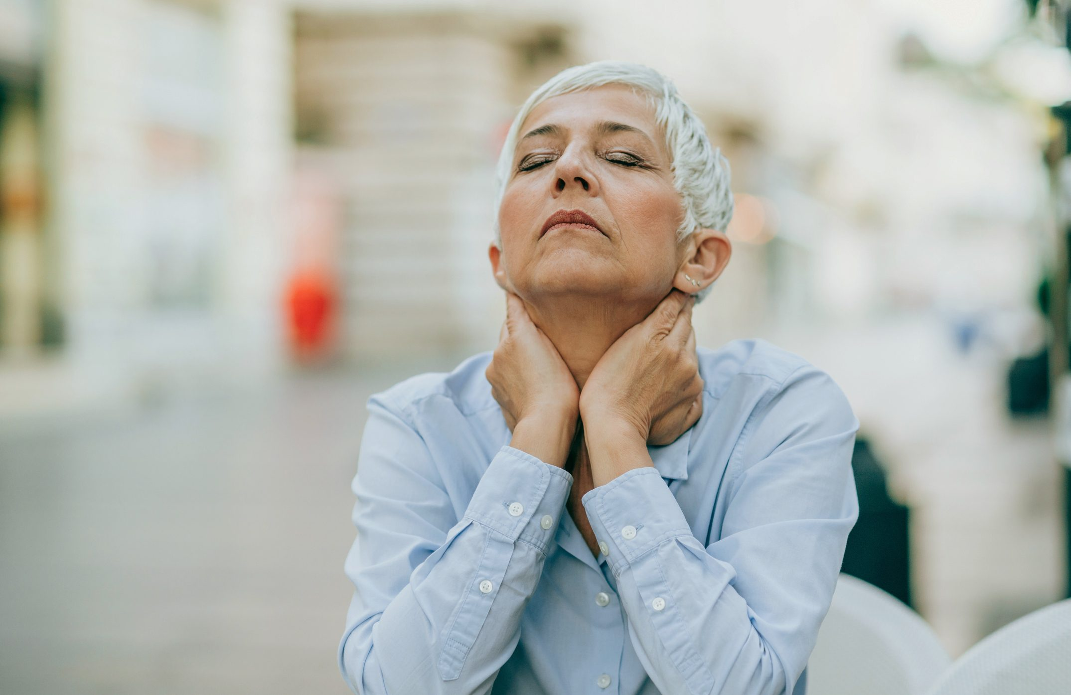 mature woman with eyes closed and hands on her neck