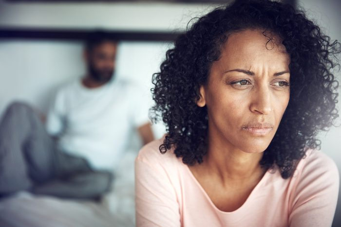 upset woman sitting on the edge of the bed with man in the background