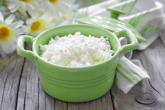 Green bowl of cottage cheese sitting on a wooden tabletop near a bunch of white flowers and a white and green cloth napkin.