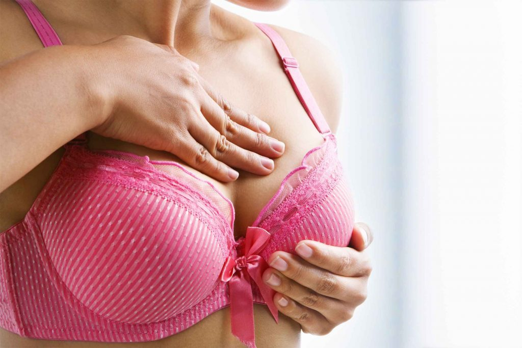 woman in pink bra checking her breasts
