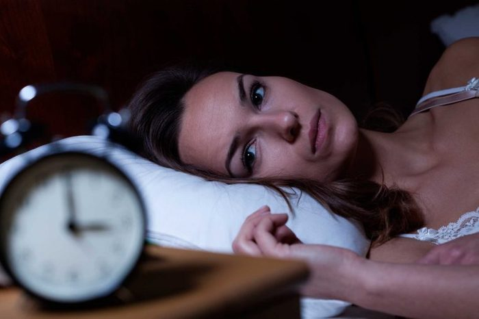 Wide-awake woman looking at her nightstand clock.