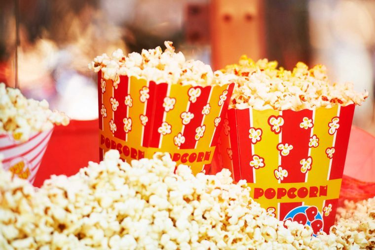 Bags of popcorn in red- and yellow-striped containers.