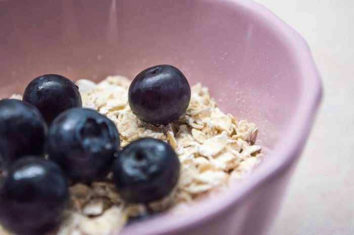 Purple bowl of oatmeal with blueberries.