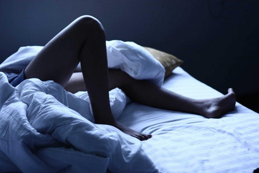 man's legs in bed