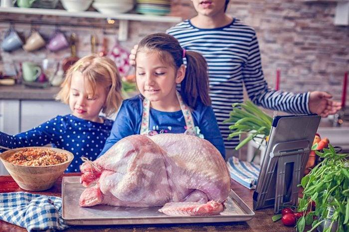 family prepping a raw turkey