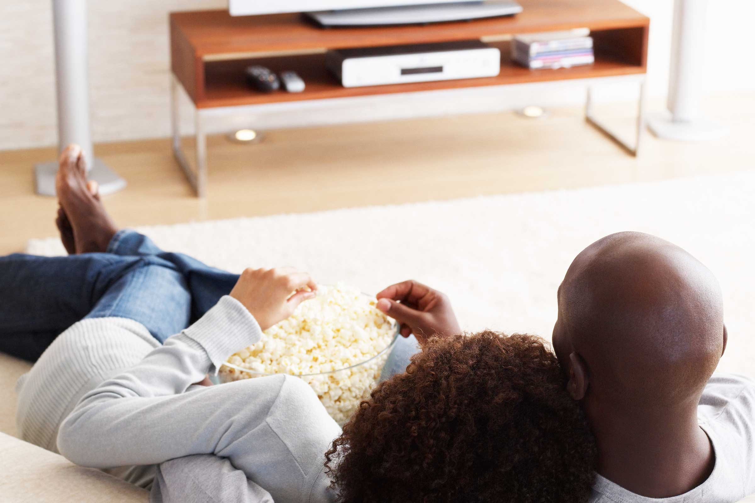Man and woman curled up on the couch together eating from a bowl of popcorn.