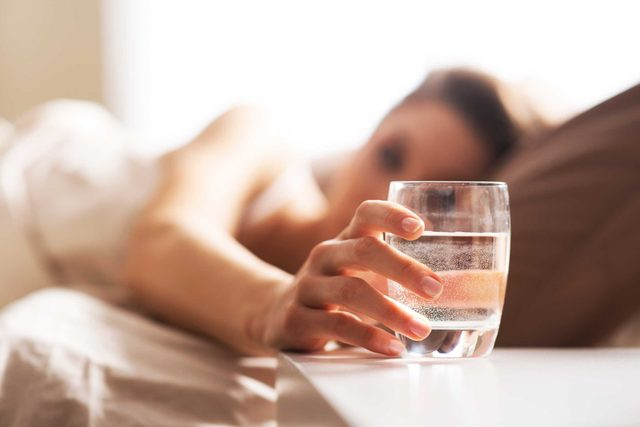 Woman in bed reaching for a glass on water on her nightstand.