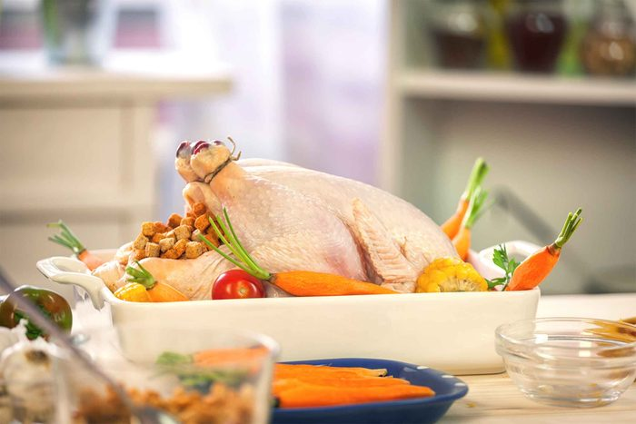trussed and stuffed raw turkey in roasting dish