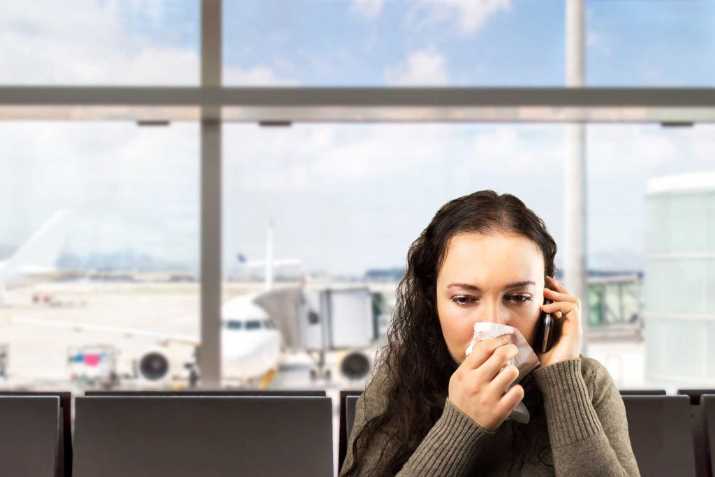 woman at the airport on the phone, blowing her nose into a tissue