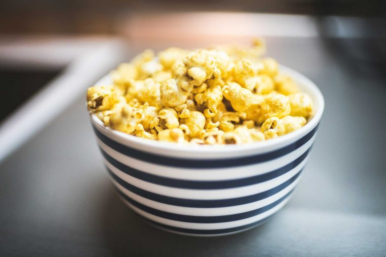 Bowl of yellow, buttery popcorn in a blue- and white-striped bowl.