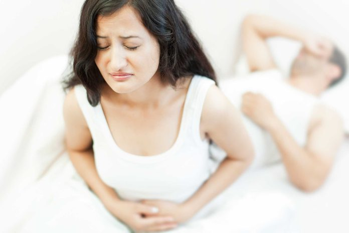 unhappy woman holding gut