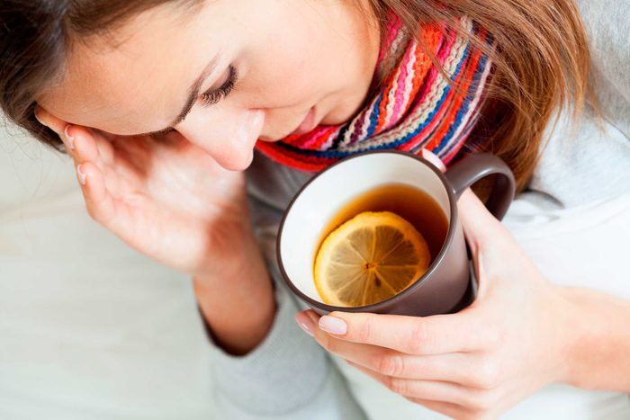 woman holding mug of tea with lemon with one hand and forehead with the other